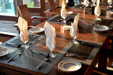 51867937 - empty glass with napkin and silverware on table for dinner setting