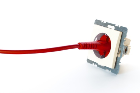 16828488 - red power cable plugged into wall outlet against white background