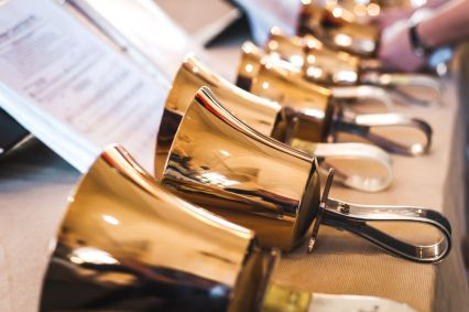 53832700 - golden handbells on table with sheet of notes