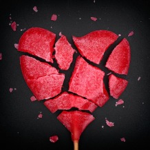 42161286 - broken red heart shaped lollipop. closeup. vignette.