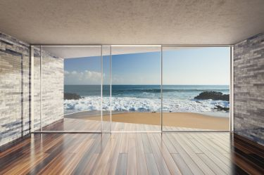 45663868 - empty modern lounge area with large bay window and view of sea