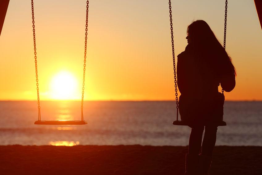 Single woman alone swinging on the beach