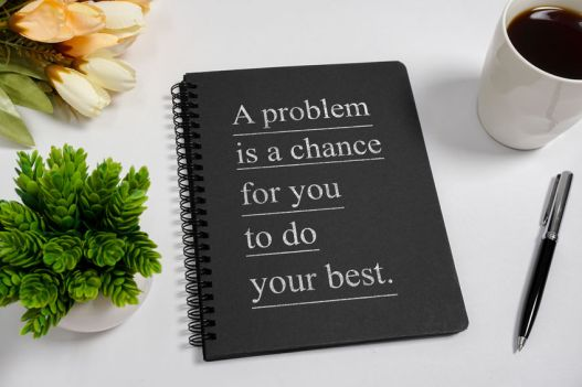 Notebook with wisdom quote and coffee cup.