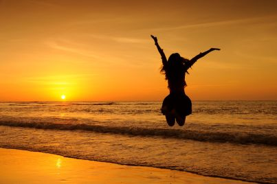 44337335 - happy woman jumping in sea sunset