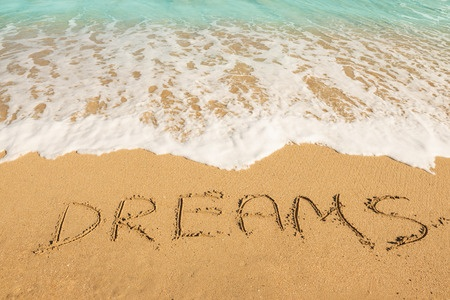 49150747 - dreams message on the beach sand - vacation and travel concept