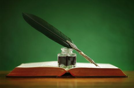 Quill pen and inkwell on old book